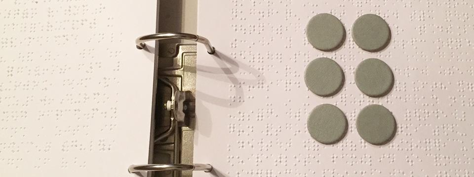 Das Bild zeigt einen Ordner mit Blindschrift-Seiten, darauf liegen sechs Punkte, um die Struktur der Blindenschrift zu zeigen.